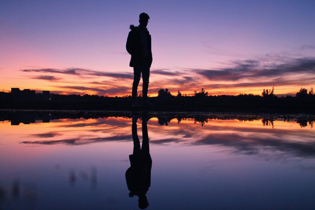 Deze afbeelding illustreert een man die zijn eigen reflectie aanschouwt als ware het een kijkje in de spiegel