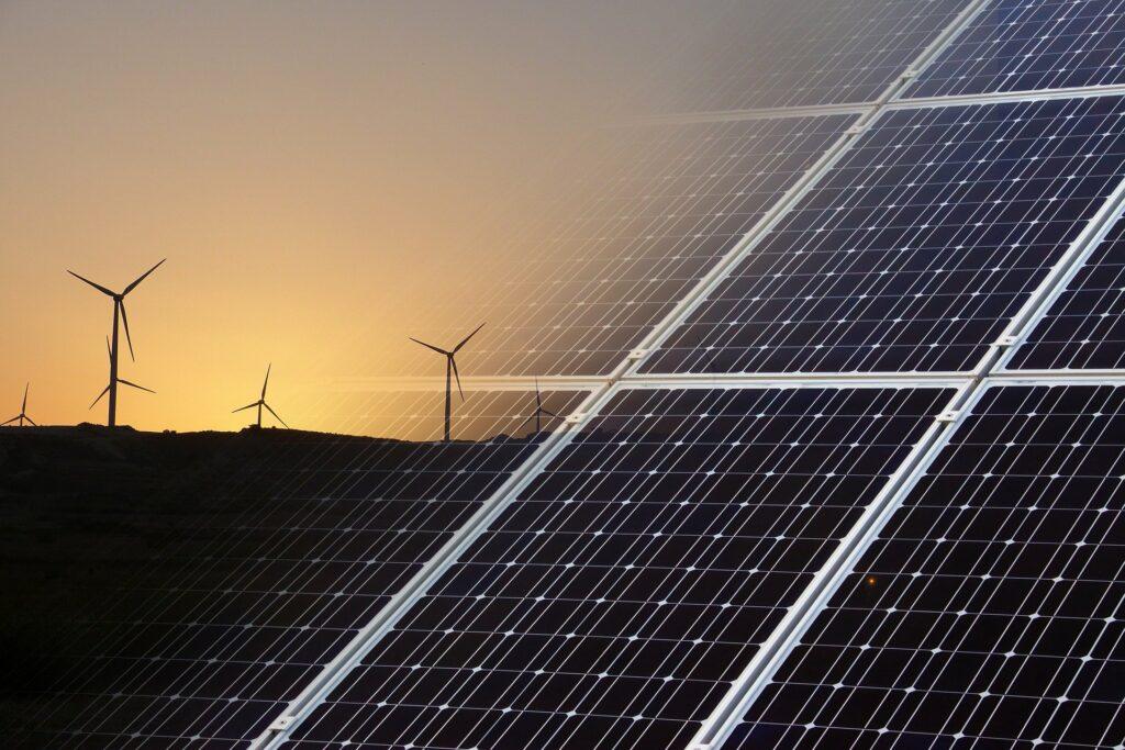 De energietransitie geïllustreerd aan de hand van zonnepanelen en windmolens